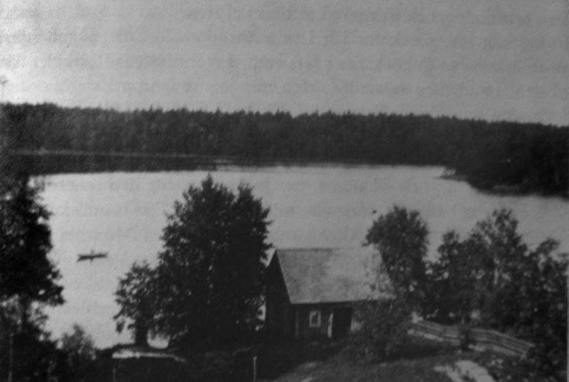 Prästgårdssjön på trädgårdens mer vildvuxna baksida. Det lilla brygghuset är omgivet av träd och buskar och trädgården avgränsas till höger i bild av en gärdsgård. Bilden är tagen kring 1920.